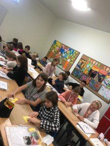 Uczniowie podczas pracy na zajęciach z techniki. Każdy pochyla się nad ławką na której ma umieszczone różne materiały.