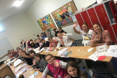 Uczniowie siedzą w ławkach na lekcji techniki i machają do aparatu.