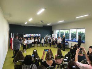 Pani Dyrektor stojąca po prawej stronie zdjęcia przemawia do uczniów przez mikrofon. Uczniowie ustawieni są w półokręgu na sali teatralnej. Na zdjęciu widoczna jest również stojąca obok Wychowawczyni klasy oraz część gości siedząca na krzesełkach i robiąca zdjęcia uczniom.