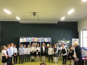 Pani Dyrektor stojąca po prawej stronie zdjęcia przemawia do uczniów przez mikrofon. Uczniowie ustawieni są w półokręgu na sali teatralnej.