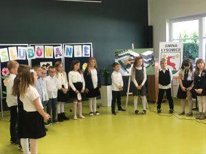 Uczniowie klasy pierwszej stoją w półkolu na sali teatralnej.