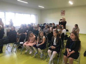 Zdjęcie gości zaproszonych na ślubowanie pierwszej klasy - rodzice uczniów i ich starsi koledzy z klasy drugiej siedzą na krzesełkach. Część rodziców na siedząco lub na stojąco wykonuje zdjęcia swoim dzieciom.