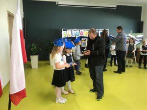 Uczniowie klasy pierwszej stoją wraz z rodzicami w grupkach na sali teatralnej i oględają otrzymane prezenty. Na głowie mają niebieskie birety.