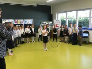 Uczniowie klasy pierwszej stoją w półokręgu na sali teatralnej. Na środku przed nimi stoi uczennica z mikrofonem.