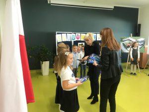 Pani Dyrektor wraz Wychowawczynią rozdje uczniom klasy pierwszej nagrody - niebieskie książeczki.