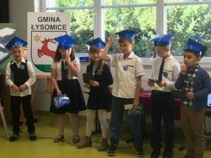Uczniowie klasy pierwszej stoją obok siebie z niebieskimi biretami na głowach. W rękach trzymają książki które dostali.