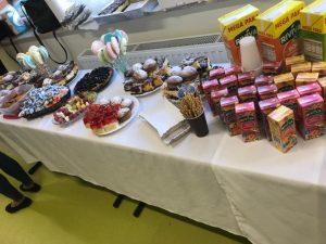 Zdjęcie poczęstunku przygotowanego dla uczniów. Na stołach zakrytych białymi obrusami ułożone na talerzacg ciasta, w kubeczkach lizaki i paluszki oraz soczki w kartoniku.
