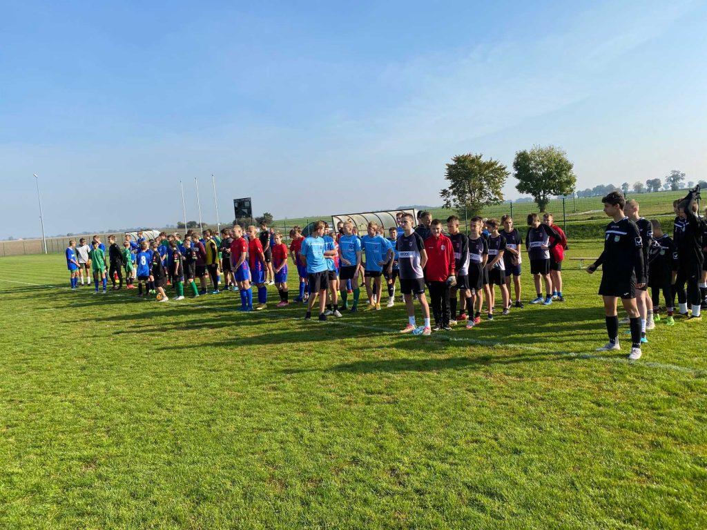 Zawodnicy biorący udział w turnieju piłki nożnej stoją w rzędach na murawie boiska.