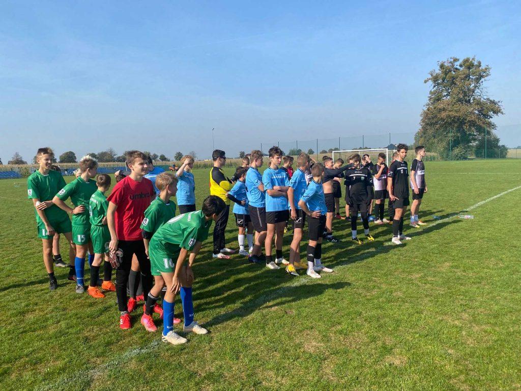Trzy drużyny biorące udział w turnieju piłki nożnej stoją w rzędach na murawie boiska.